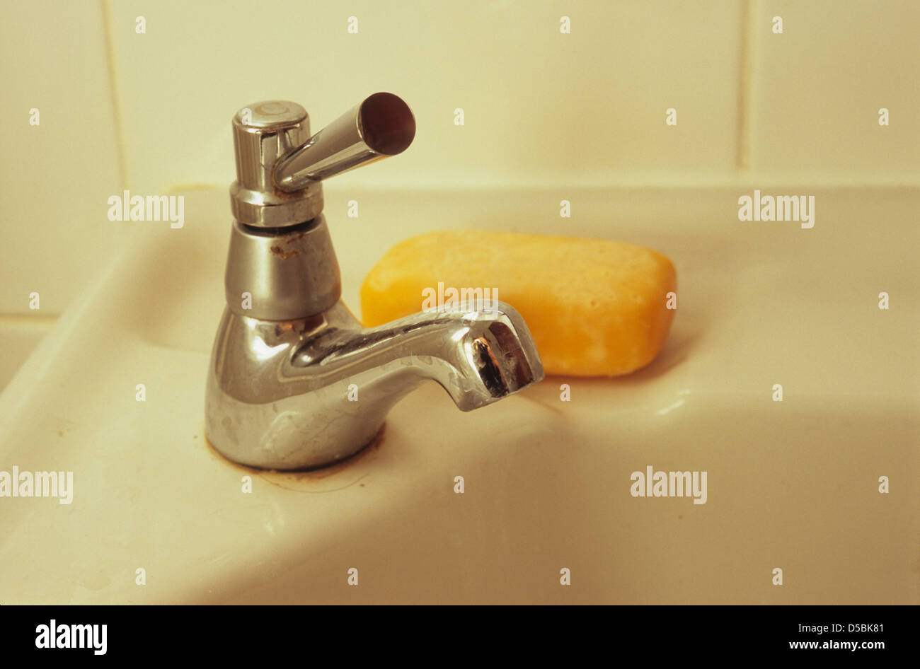 Detail of bathroom sink with tap with lever handle and bar of orange ...