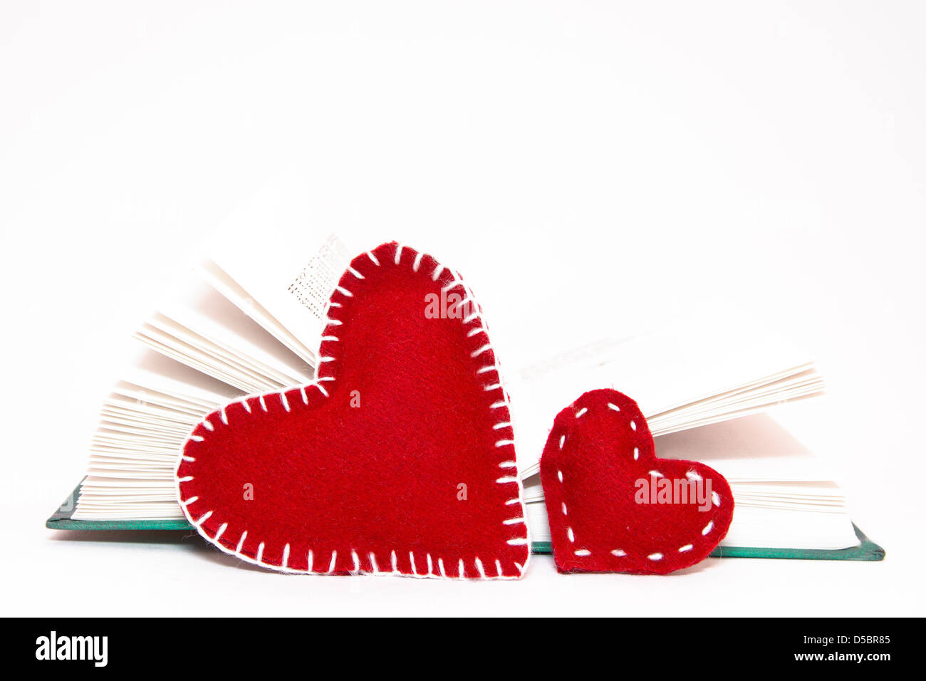 Two red heart with open book isolated on white background - Stock Image