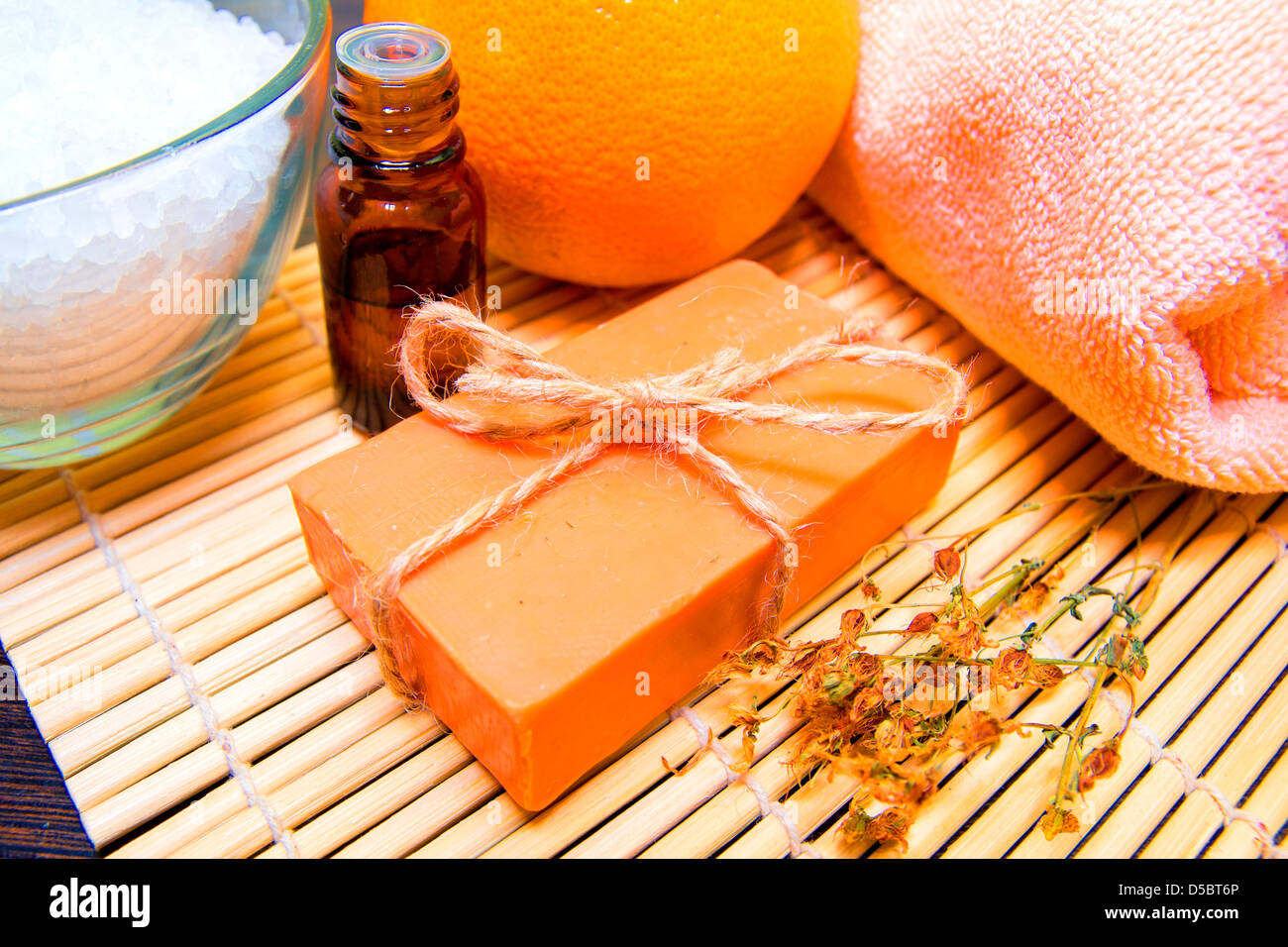 Natural handmade soap, essential oil, dried herbs, bath salt, orange and towel on bamboo mat. Spa concept. - Stock Image
