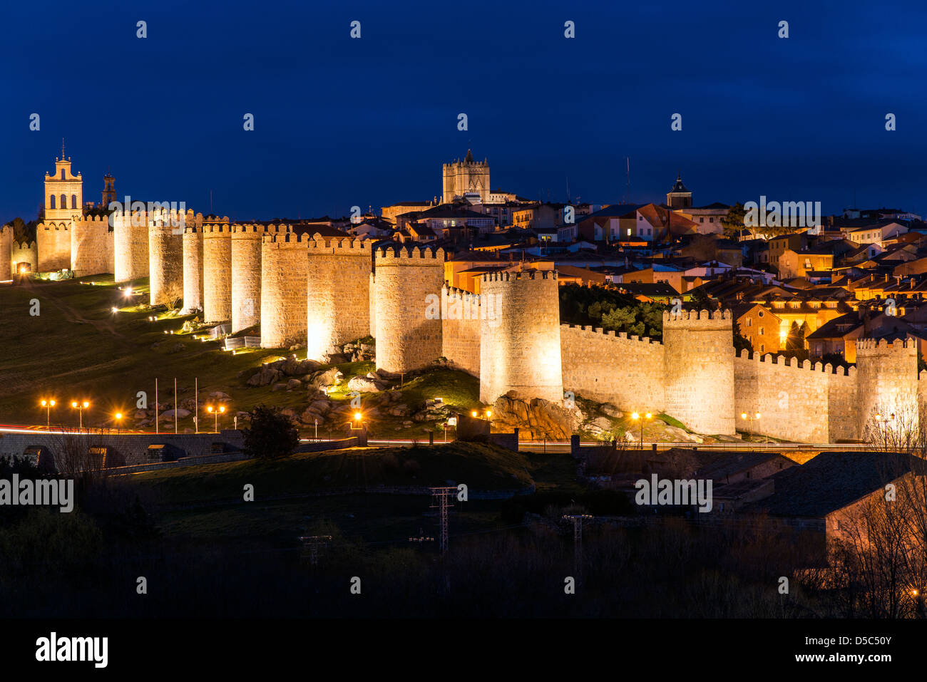 View from Cuatro Postes over the medieval city walls illuminated at night, Avila, Castile and León, Spain - Stock Image