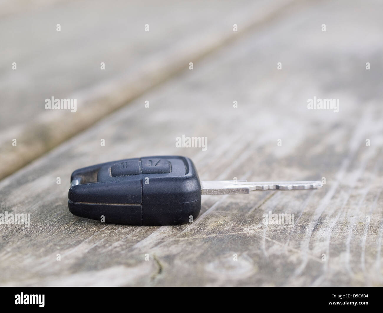 Forgotten car key on a wooden plank in a bench park. A macro detail. - Stock Image