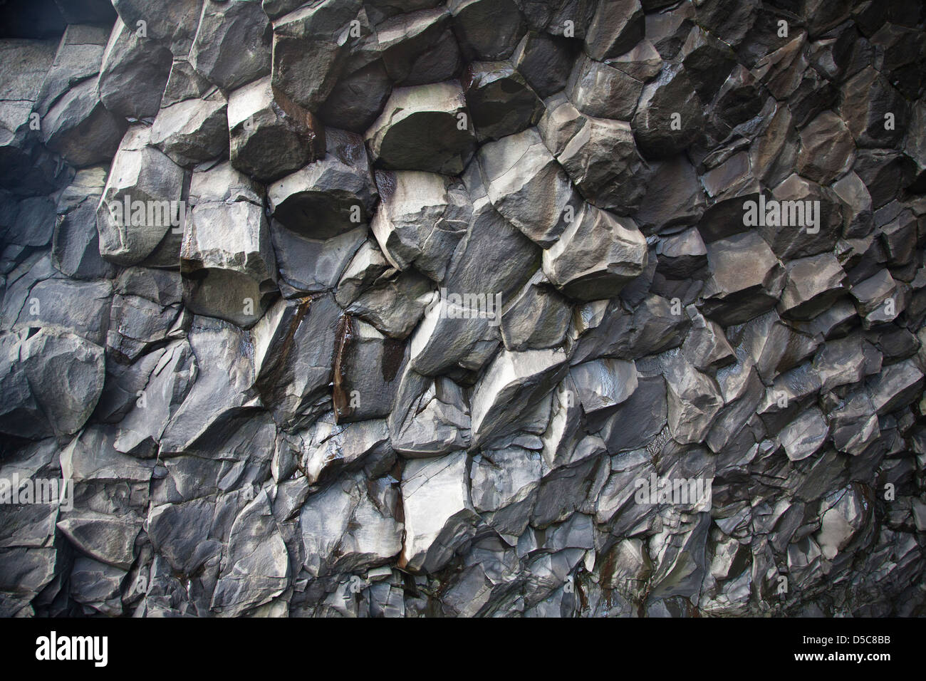 Hexagonal and pentagonal basaltic columns are the remains of old volcanic activity in Reynisfjara in southern Iceland. - Stock Image