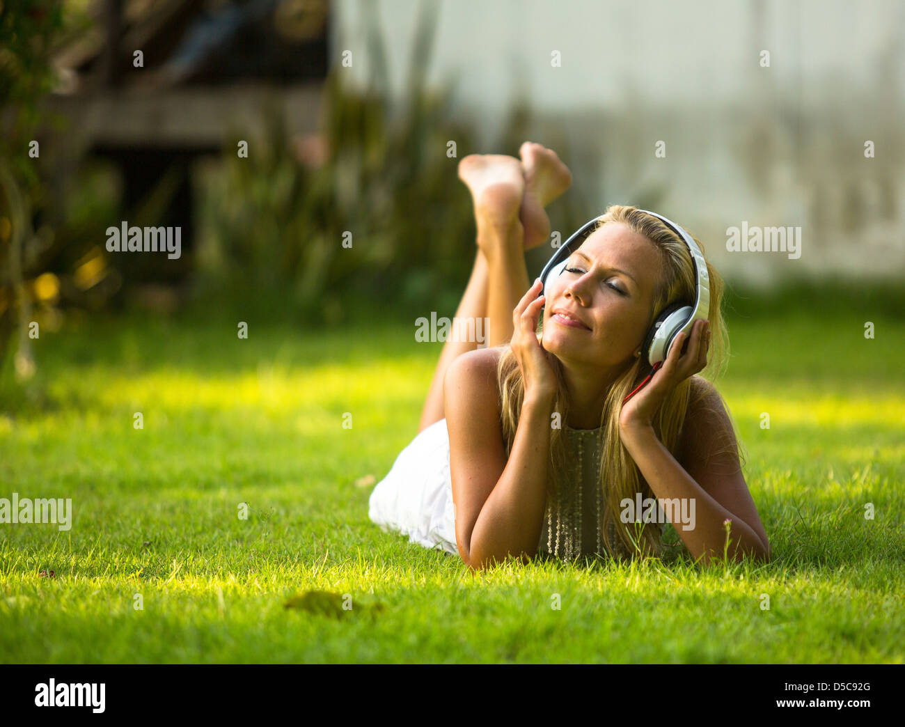 Happiness lovely girl with headphones enjoying nature and music at sunny day - Stock Image
