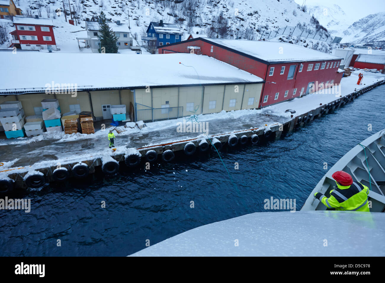 hurtigruten crew member throws ships rope guide line to dock worker oksfjord during winter norway europe - Stock Image