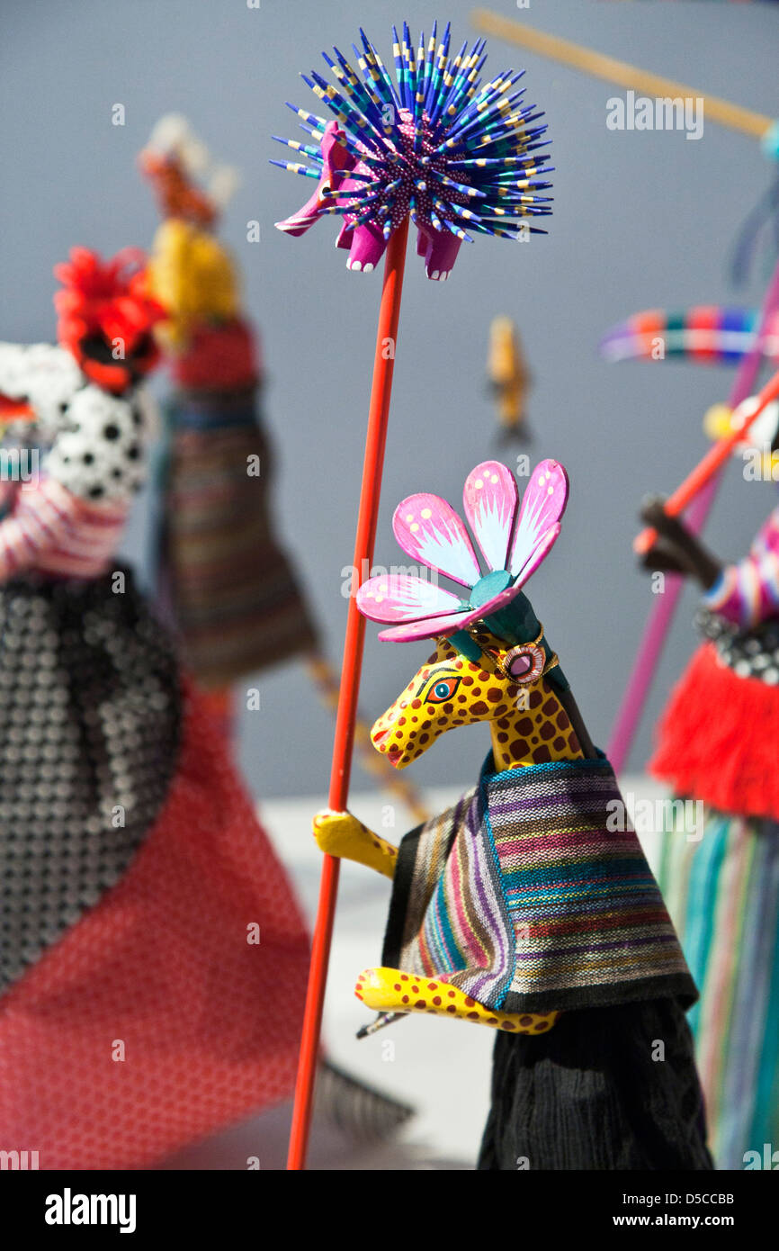 fanciful lady giraffe carrying porcupine staff in group of miniature anthropomorphic stilt dancers Oaxaca Museo - Stock Image