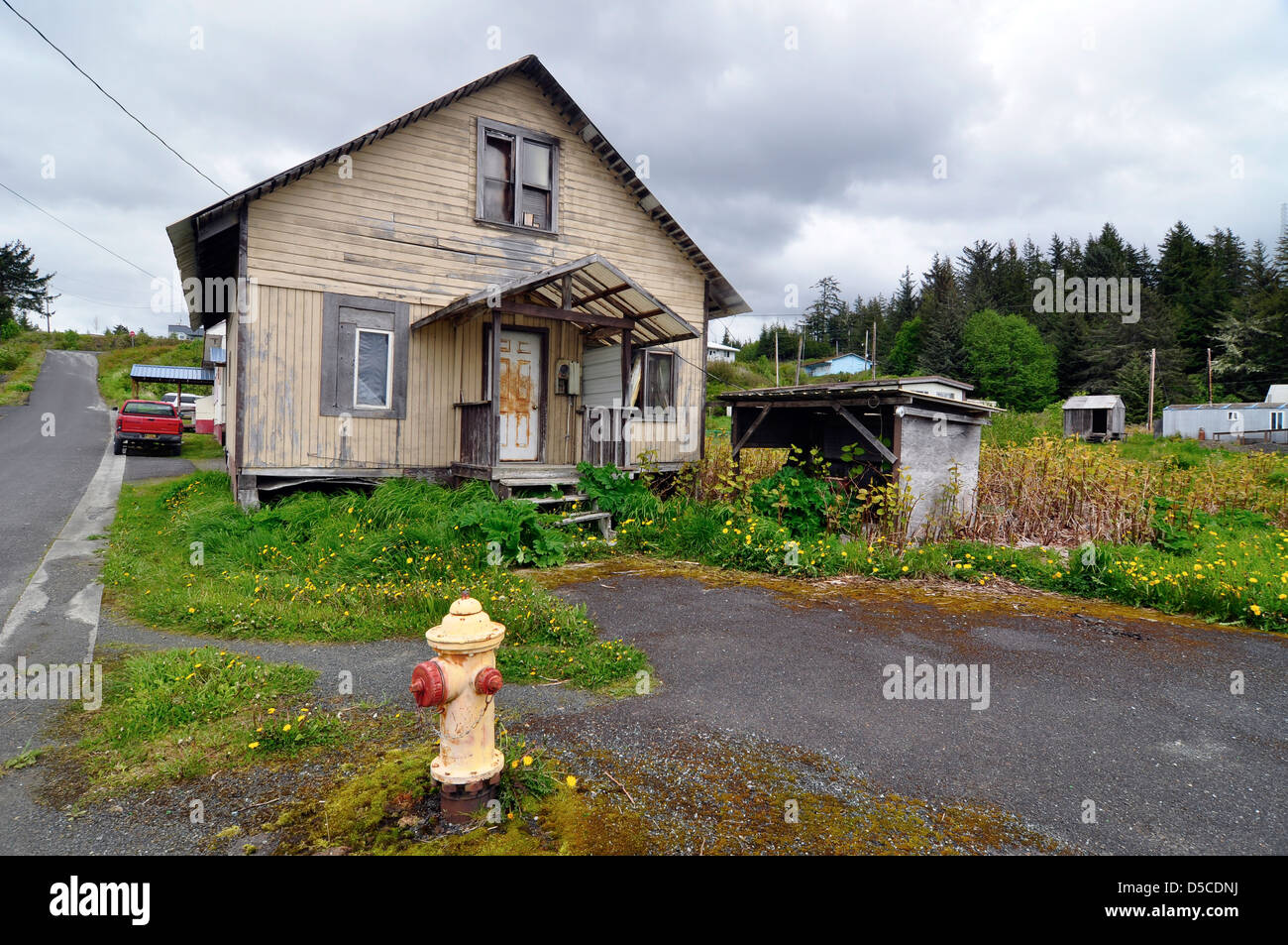 Fire hydrant in front of house in Kake, Alaska. - Stock Image