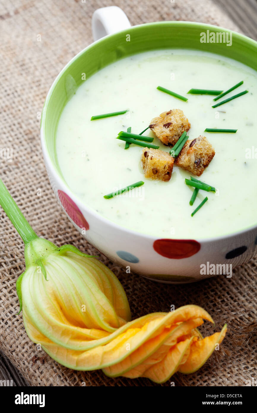 Bowl of zucchini soup with croutons and chives - Stock Image