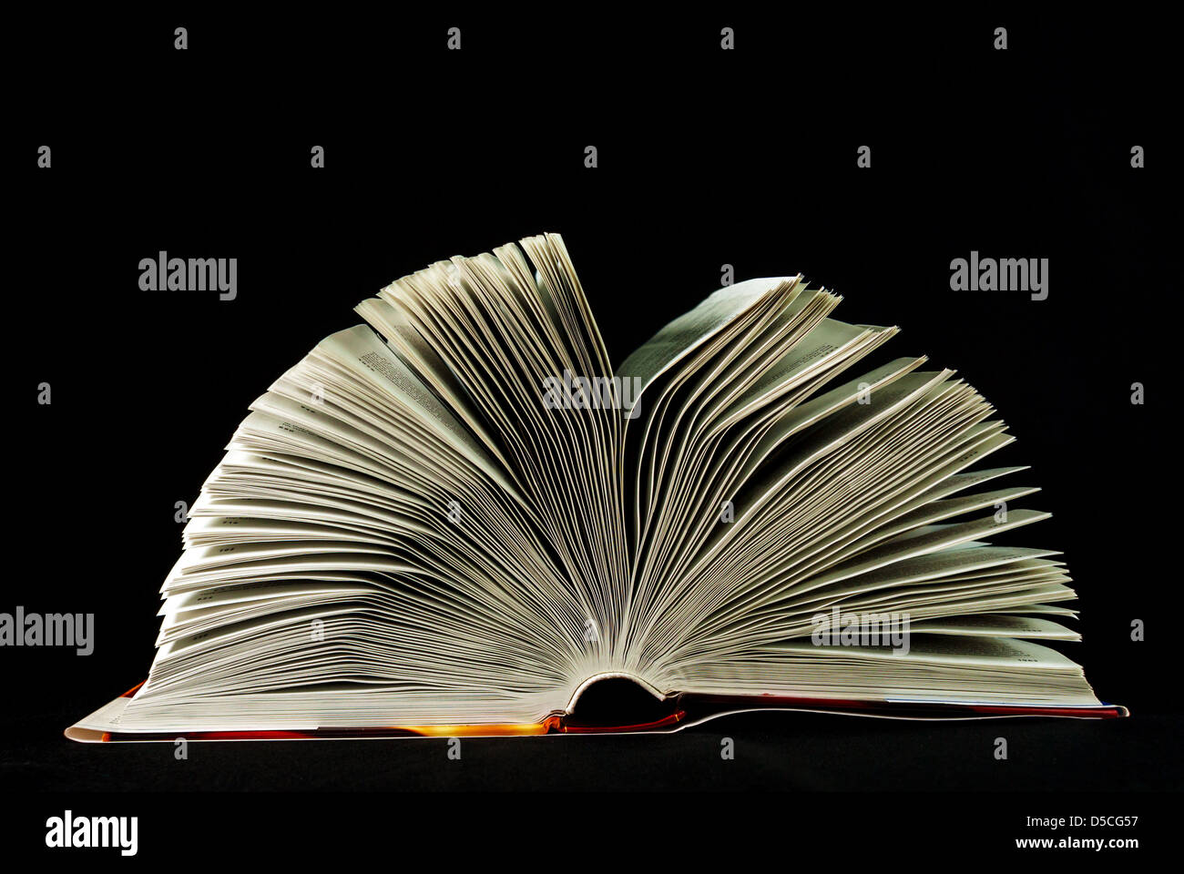 Open Bible against black background - Stock Image