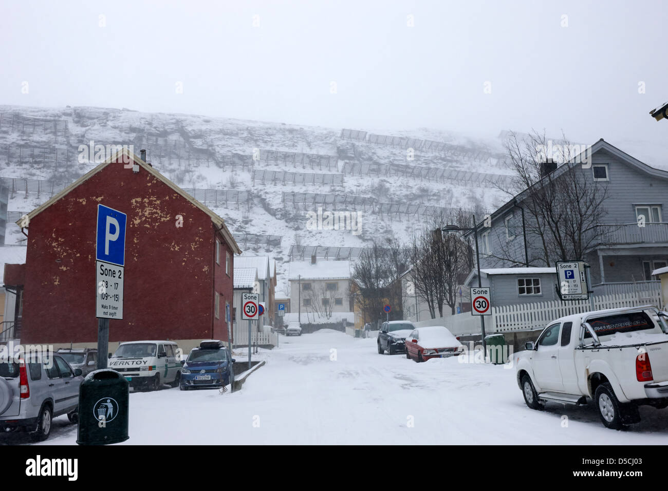 snow fences anti avalanche hill barriers on hillside above street covered in snow during winter hammerfest finnmark - Stock Image