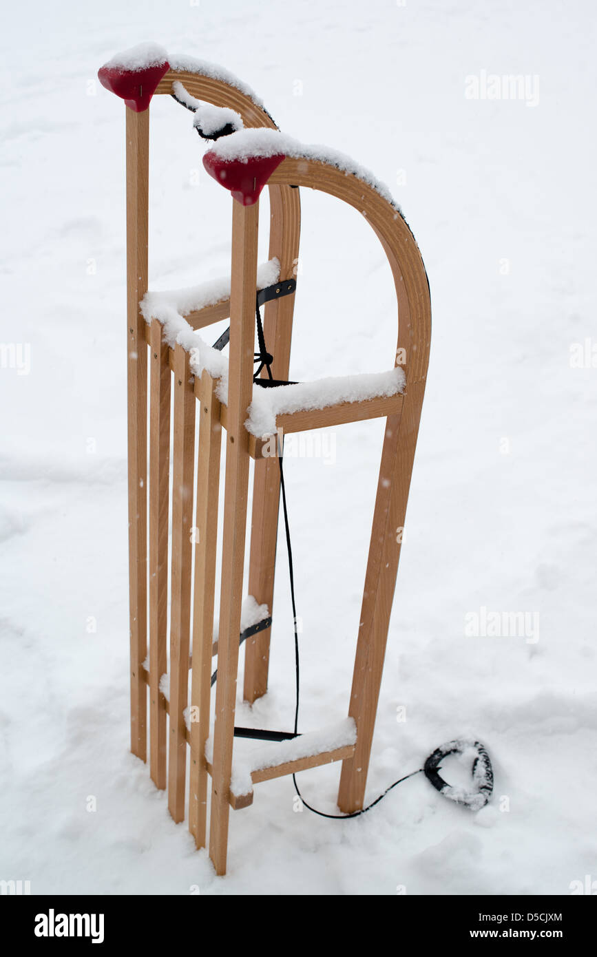 Wooden sled for a kid in fresh snow - Stock Image
