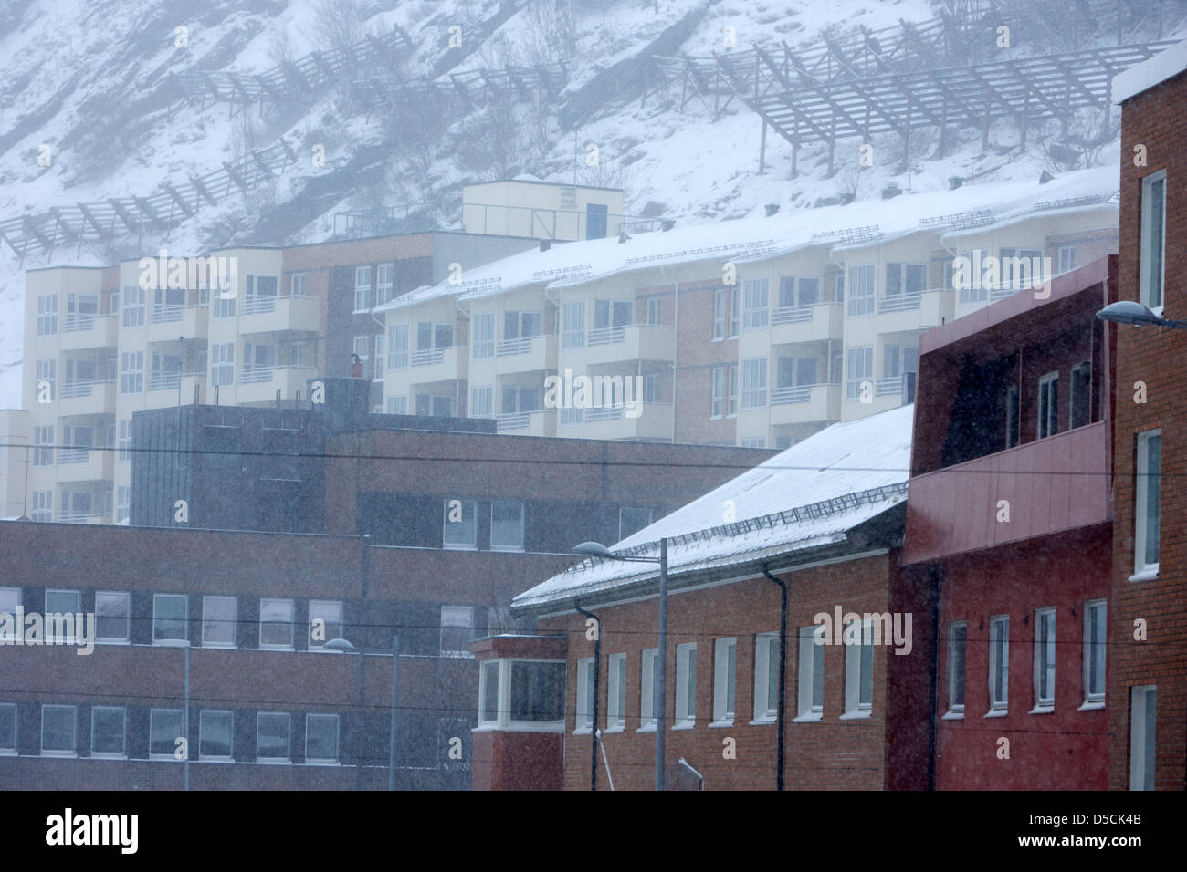 snow fences anti avalanche hill barriers on hillside above apartment blocks during winter hammerfest finnmark norway - Stock Image
