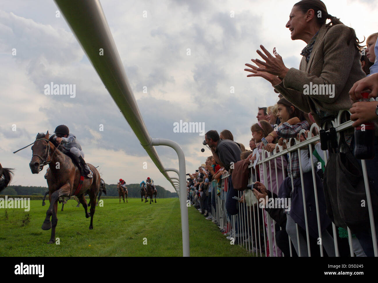 Hoppegarten, Germany, woman on a race track cheers on her horse - Stock Image