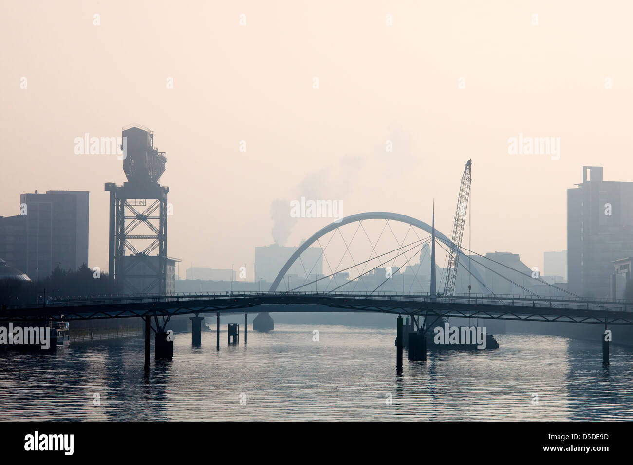 Early morning mist on the River Clyde at Finnieston and Broomielaw, showing the Bells Bridge and the Glasgow Arc, - Stock Image