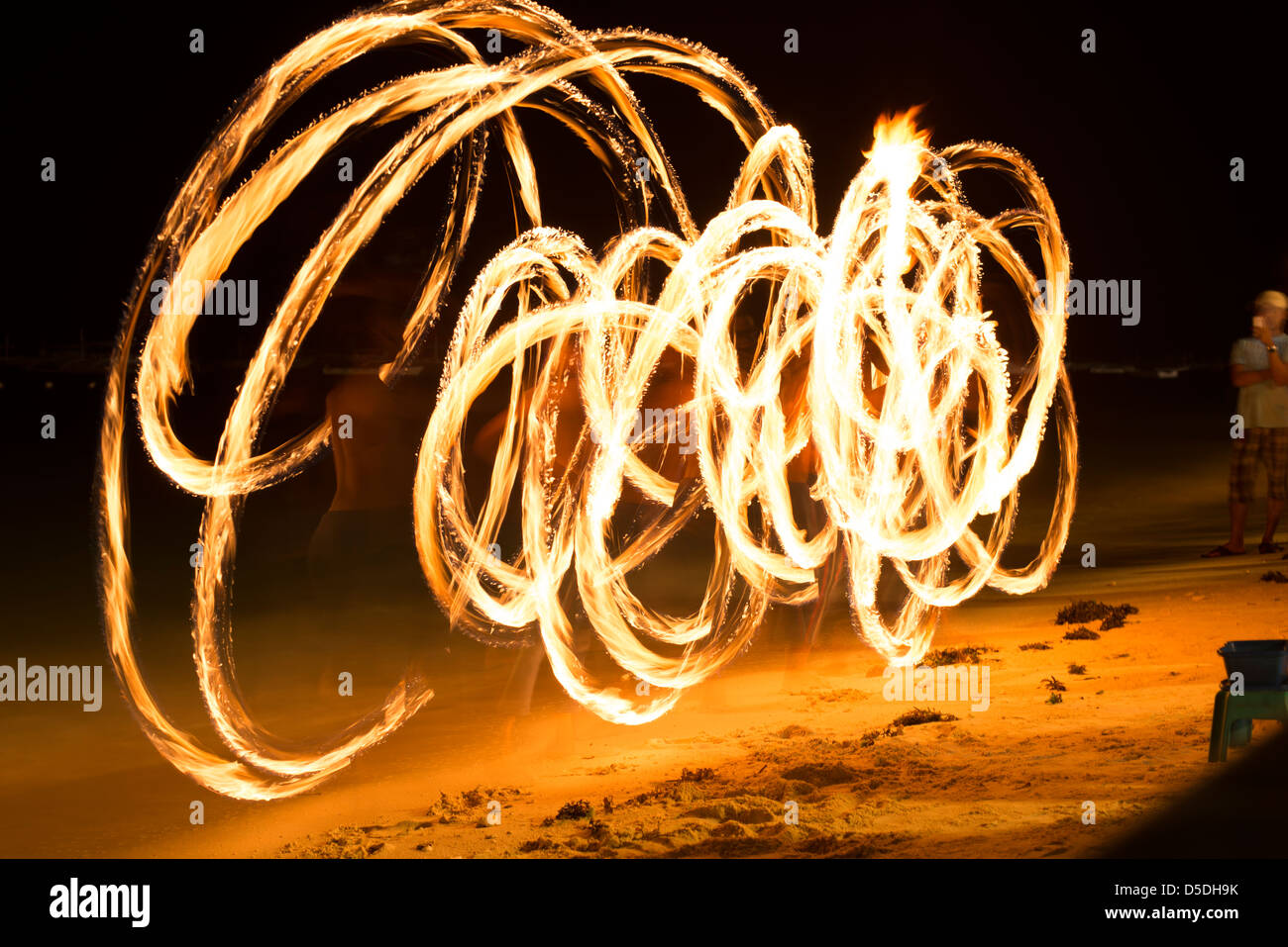 Fire artist showing off his art on Alona Beach - Stock Image