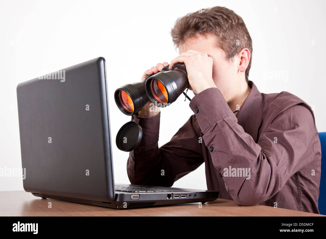 Man Searching On At A Desk With Binoculars On A Computer