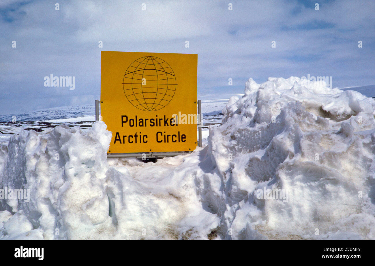 Deep wintertime snows plowed from a northern Norwegian highway almost hide a yellow roadside sign marking the Arctic Stock Photo