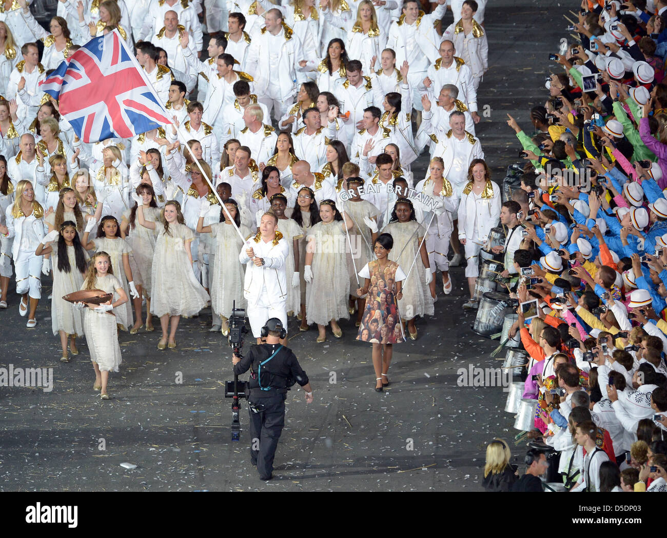 Chris Hoy (GBR, Great Britain) flagbearer leads the team around as the other athletes lean over to get a photo - Stock Image