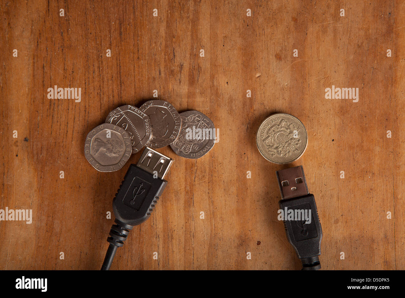 Online money transfer or bank/banking charges concept with UK coins. - Stock Image