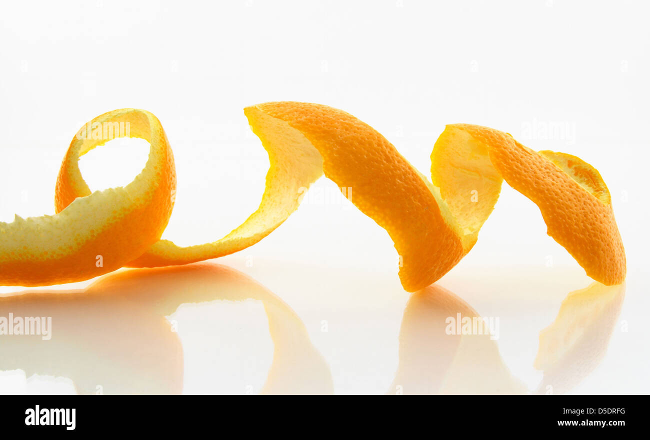 Spiral peeled skin of an orange with reflection. - Stock Image