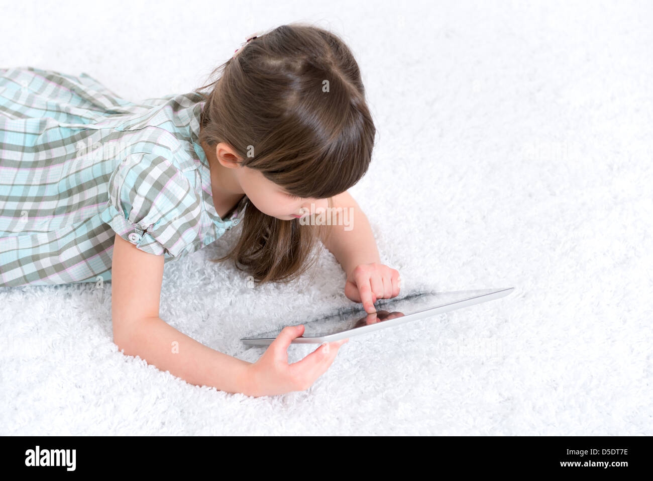 Young girl (6-7 year) looking and playing with digital tablet in a white room. - Stock Image