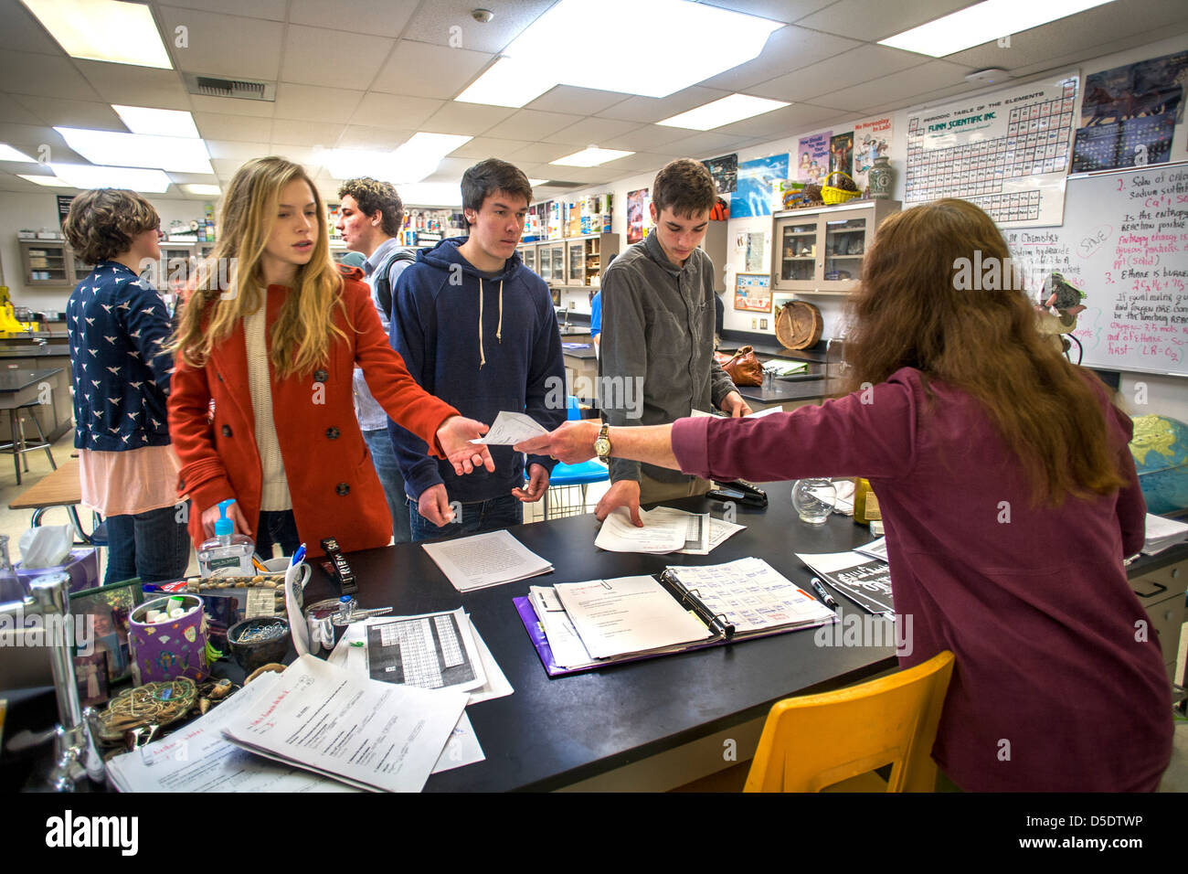 A high school chemistry teacher returns graded homework papers to her advanced placement (AP) students in San Clemente, - Stock Image