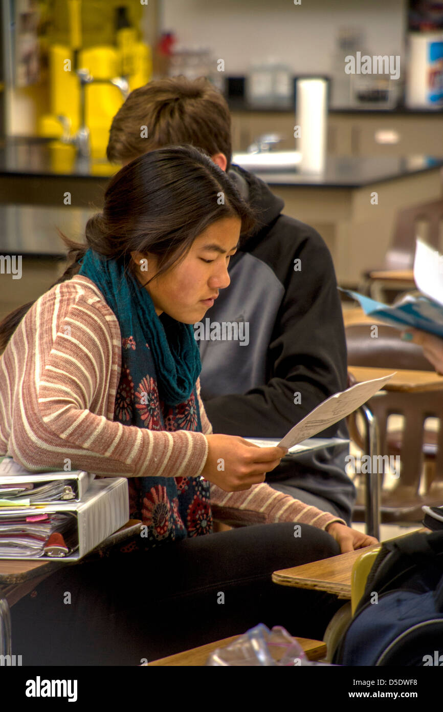 A Japanese-American advanced placement (AP) high school chemistry student reads her graded paper before class. - Stock Image