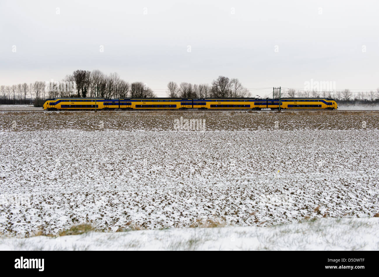 Passing yellow train of the Dutch Railways  in a snow covered landscape. Zeeland, Netherlands. - Stock Image