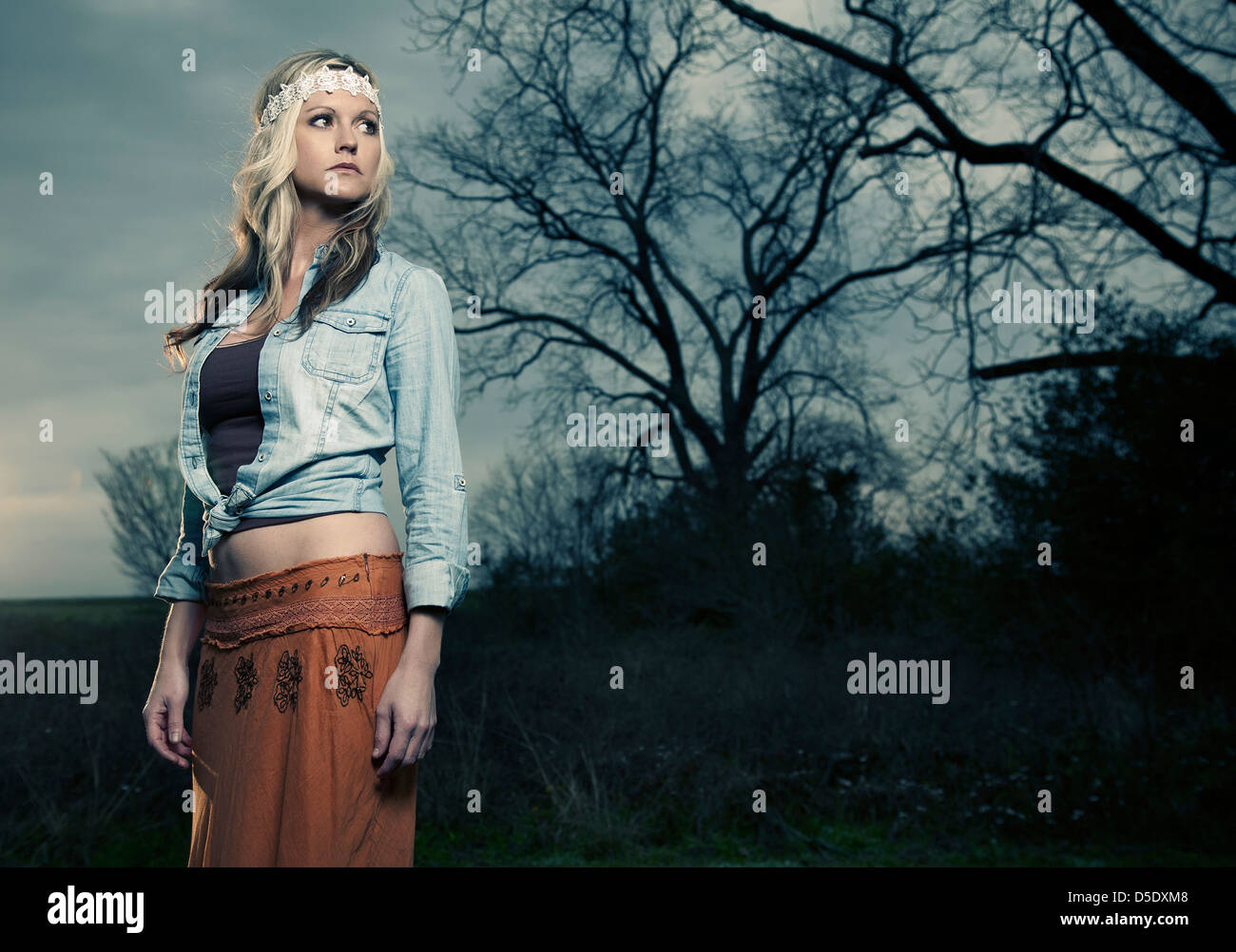 Woman sixties dress standing in field against sky - Stock Image
