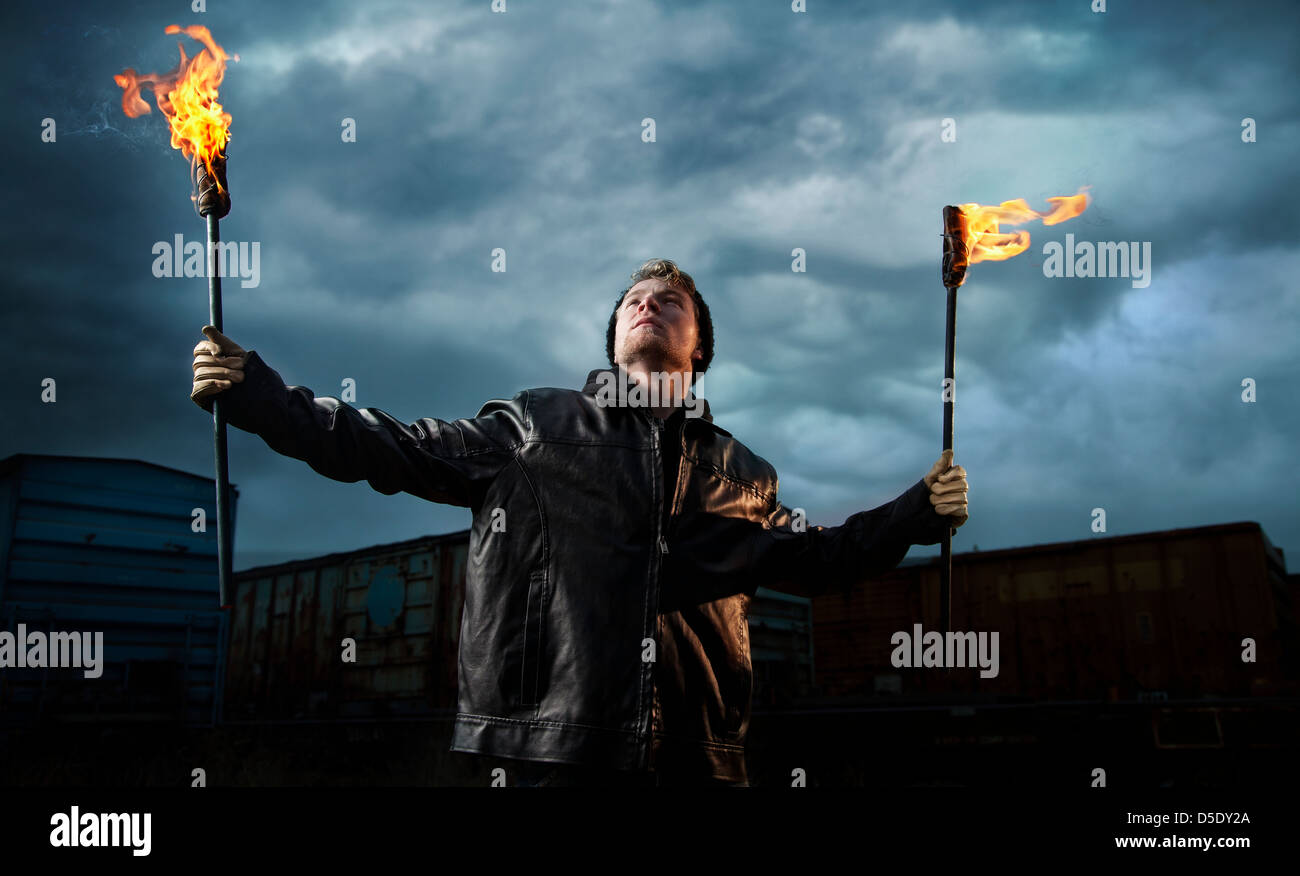Man holding torches stormy sky rail road cars - Stock Image