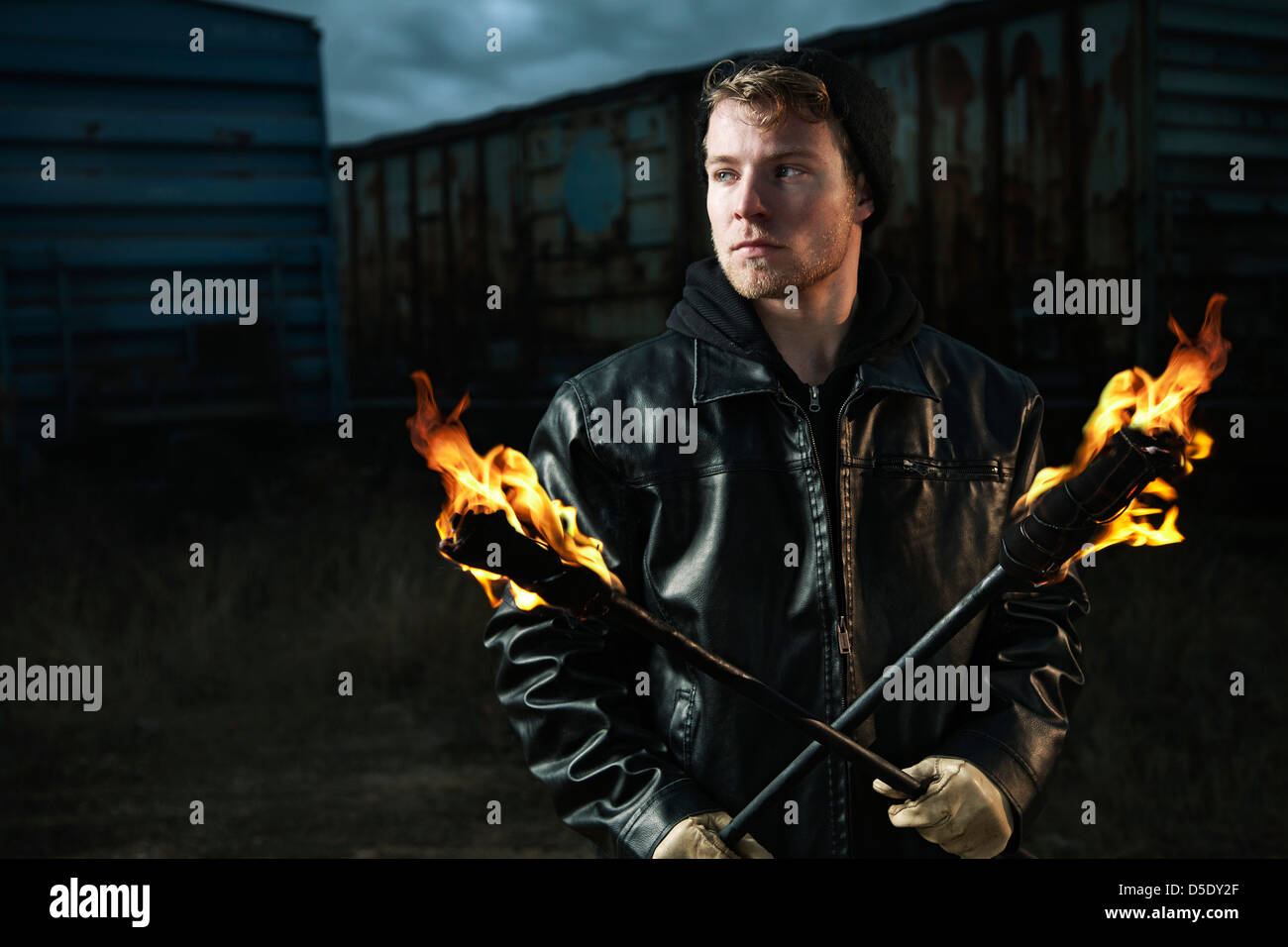 Man holding torches in rail road yard - Stock Image