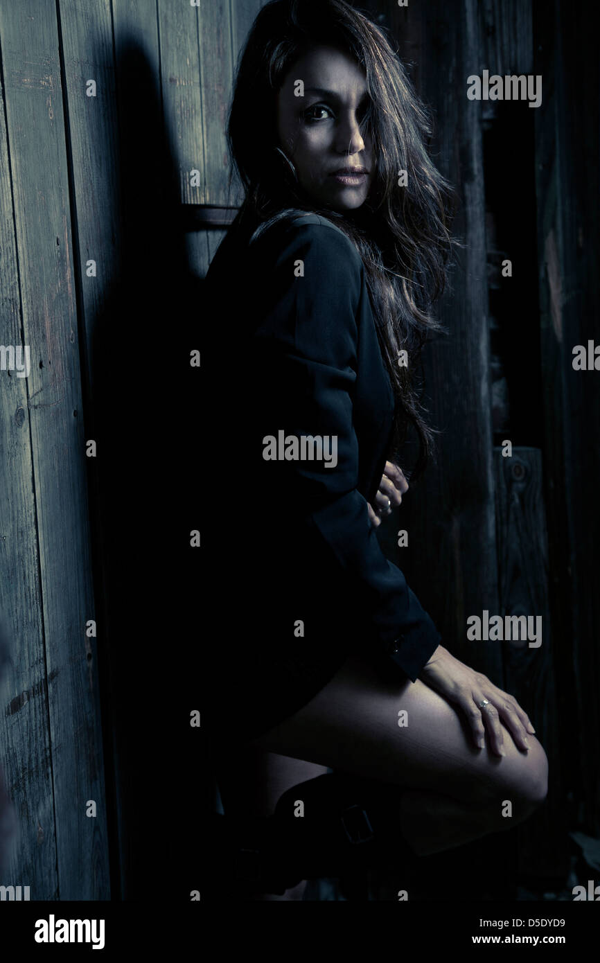 Woman leaning against wall in dark alley - Stock Image