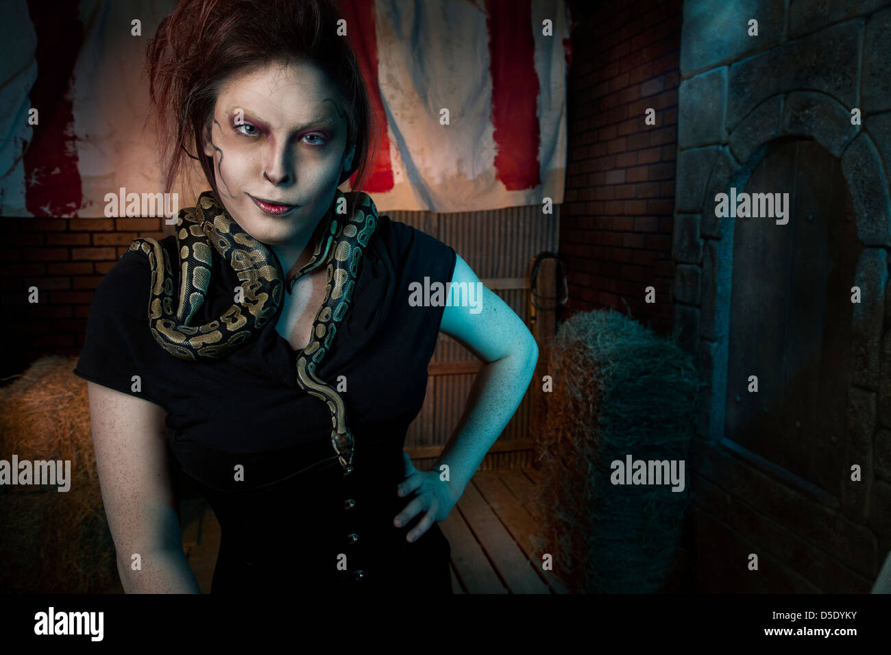 Woman with snakes around neck in tented dark alley - Stock Image