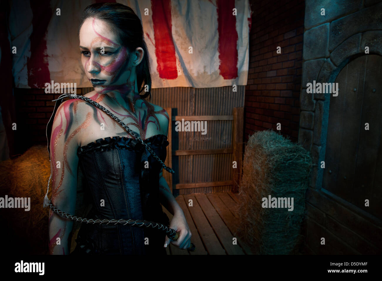 Woman with tattoos and whip in tinted alley - Stock Image