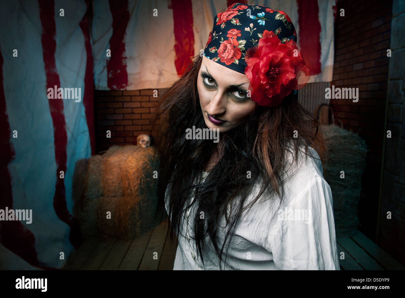 Dark gypsy woman front of dark tented alley - Stock Image