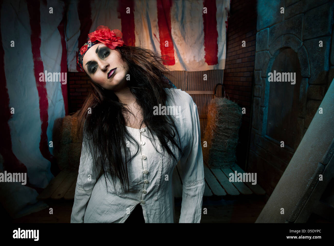 Wicked gypsy girl standing in front of creepy background - Stock Image