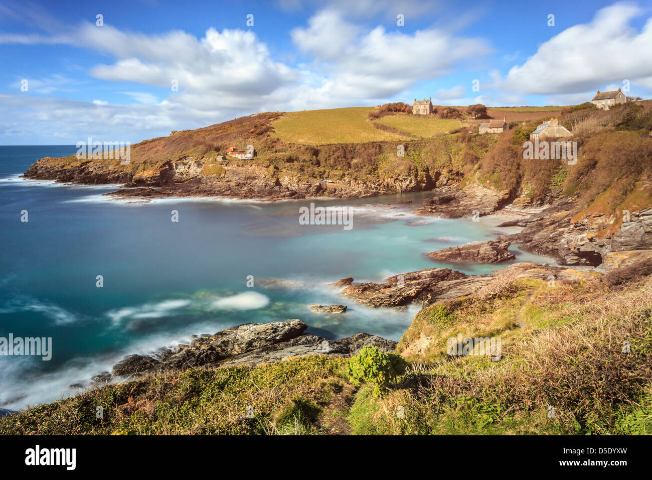 Cornwall's Prussia Cove captured using a long shutter speed to blur the movement in the sea and clouds - Stock Image