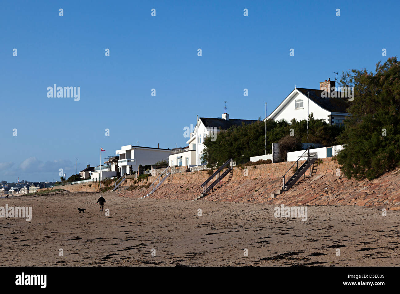 Houses with beach frontage and man walking dog, St Helier, Jersey, Channel Islands, UK - Stock Image