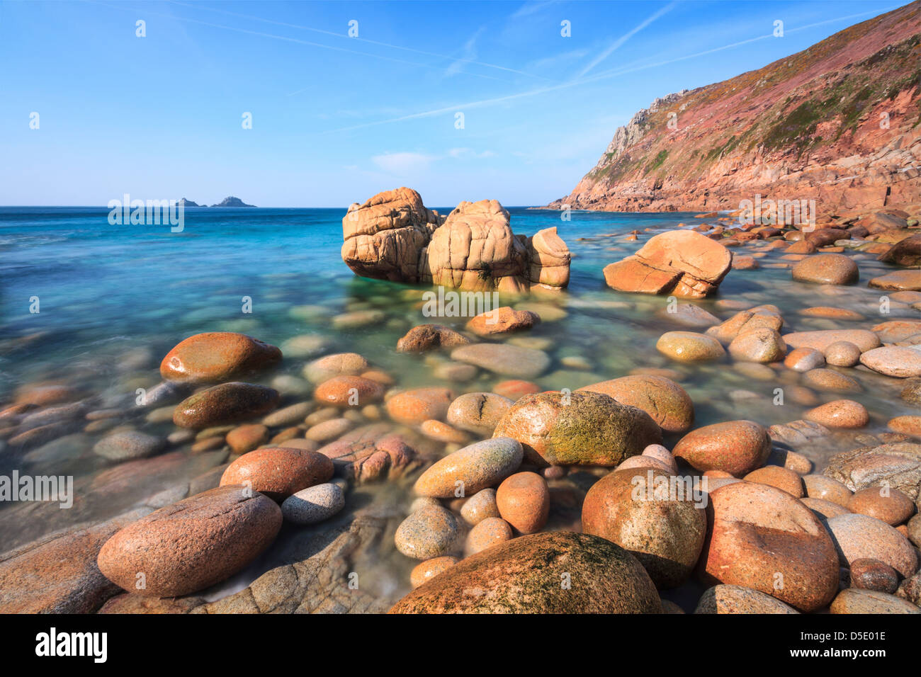 Boulders on Porth Nanven cove with Bubble Gum Rock and The Brisons in the distance.  Captured using a long shutter - Stock Image