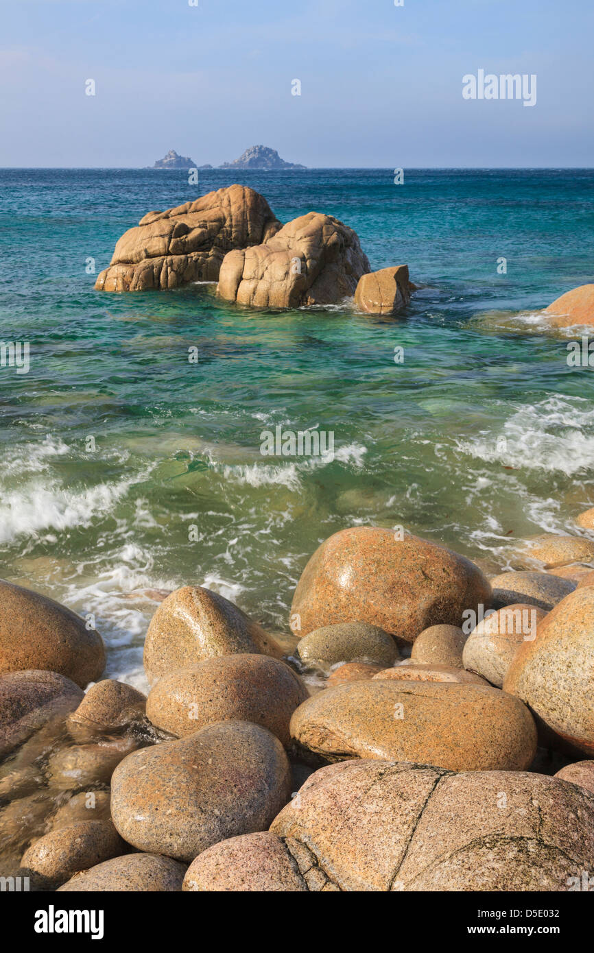 Boulders on Porth Nanven cove with Bubble Gum Rock and The Brisons in the distance. - Stock Image