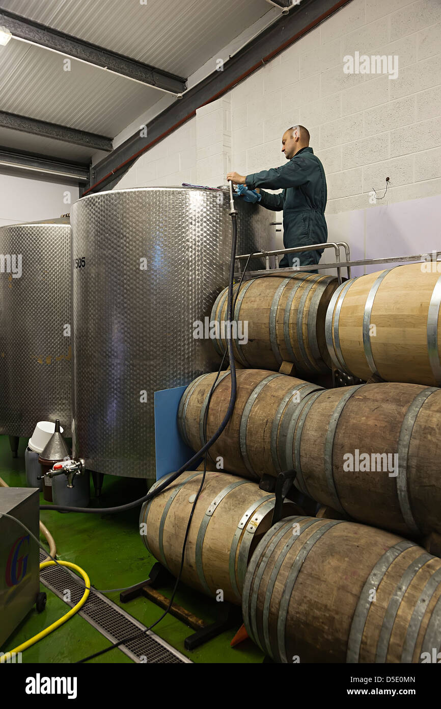 Cleaning stainless steel containers used to make wine, La Mare estate, Jersey, Channel Islands, UK - Stock Image