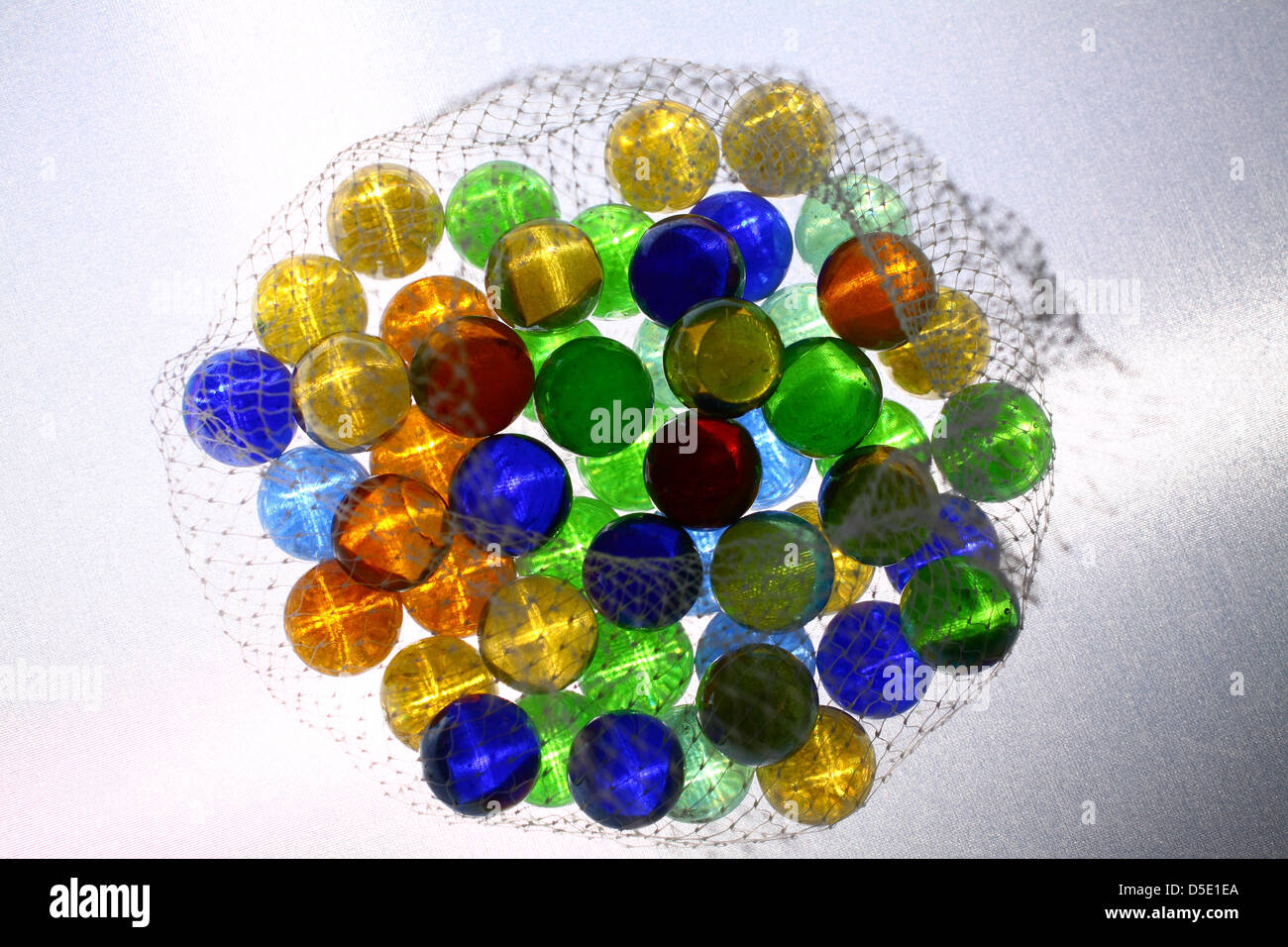 Marbles in net bag on white background - Stock Image