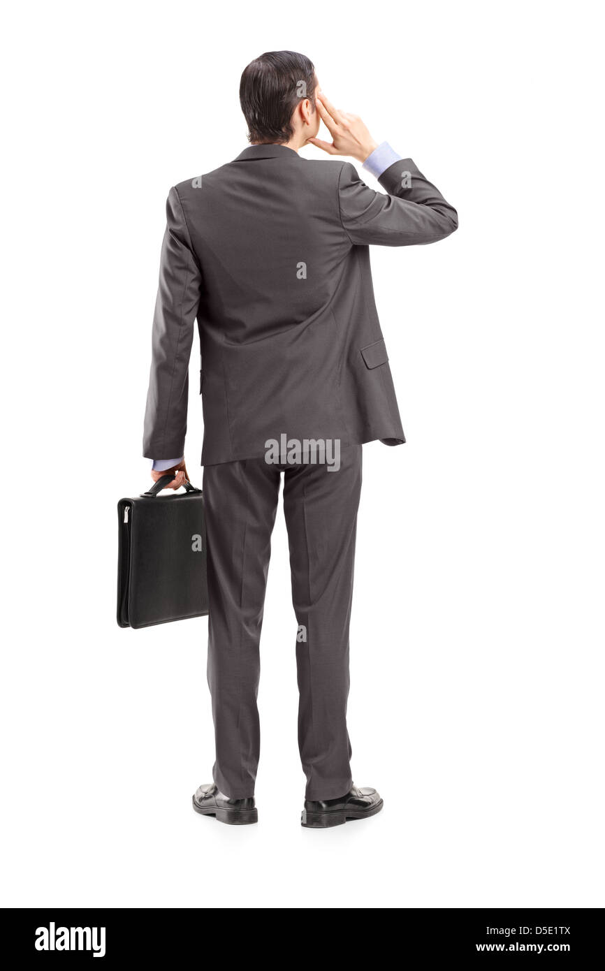 Full length portrait of a businessman thinking, shot from behind, isolated against white background - Stock Image