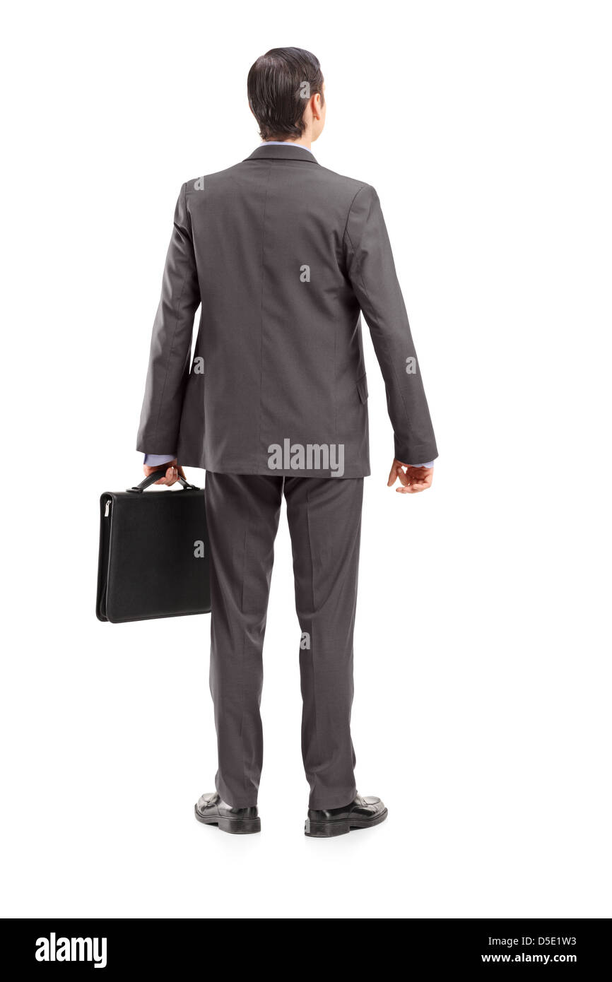 Full length portrait of a businessman with briefcase shot from behind, isolated against white background - Stock Image