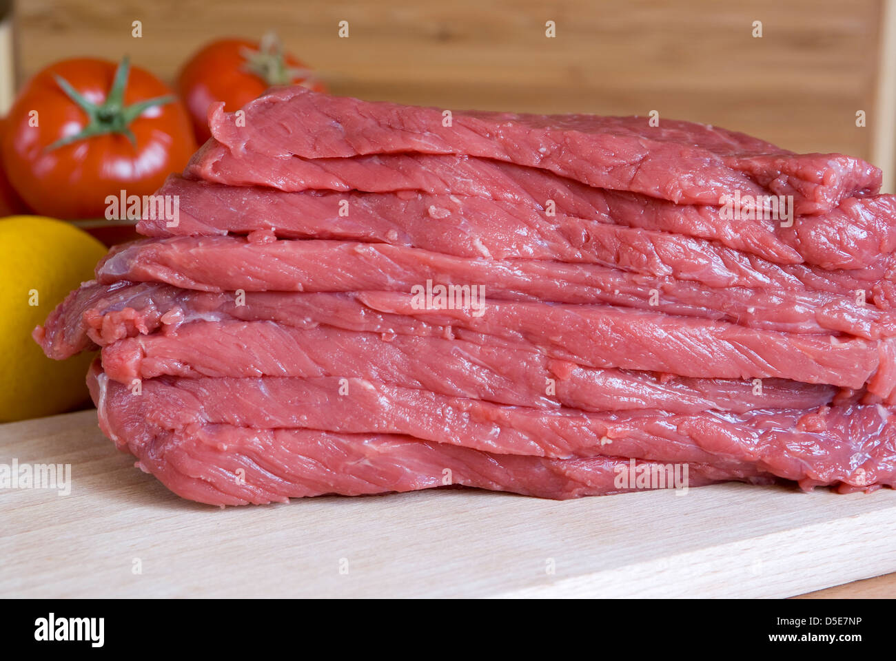 cut fresh meat beef with vegetables on plank - Stock Image