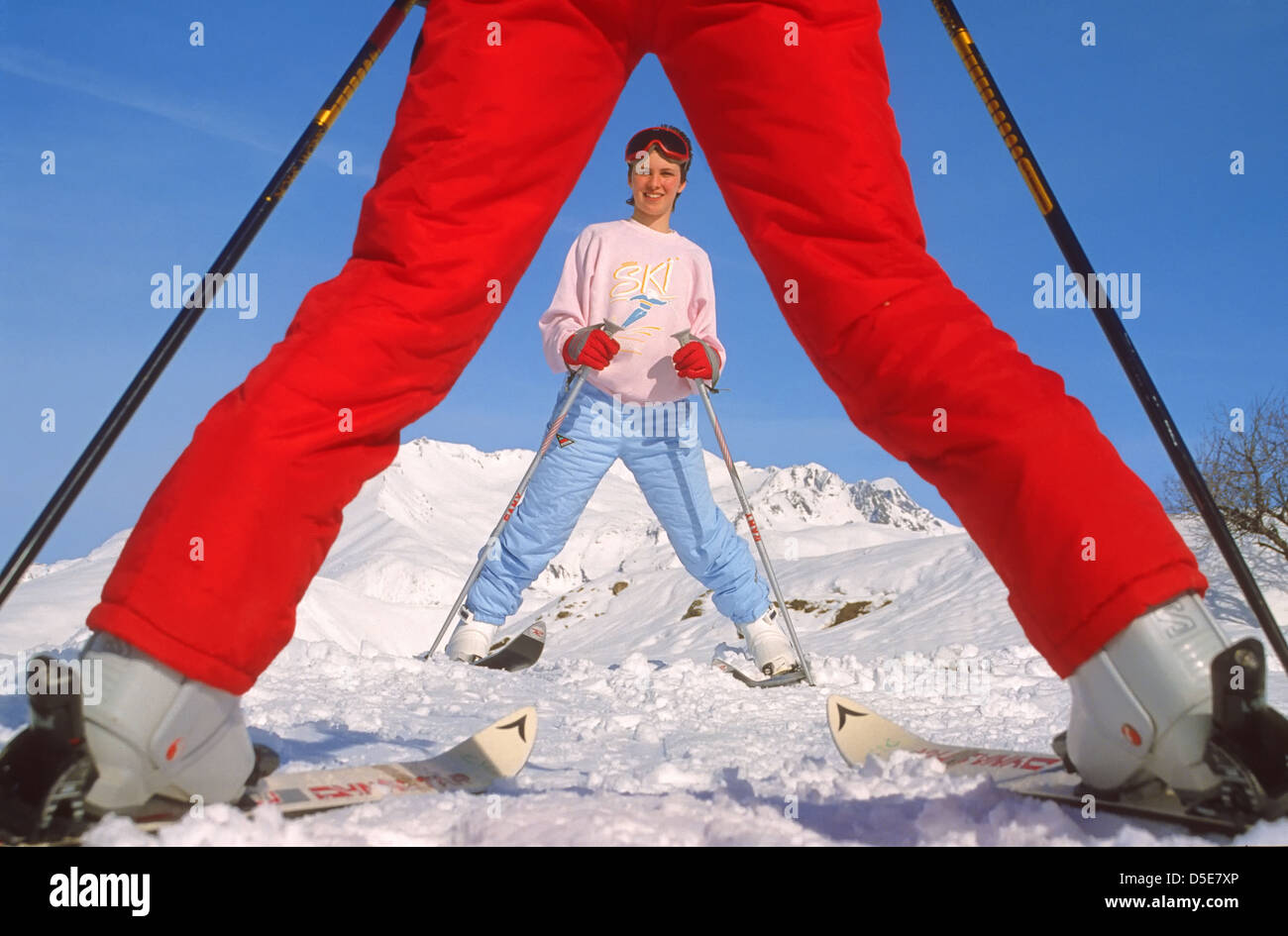 Young skier seen through ski instructor's legs Stock Photo