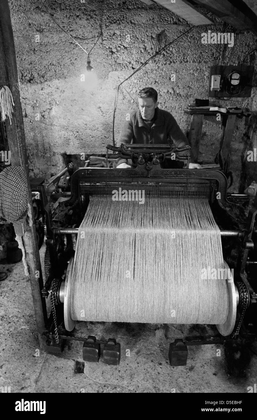 Cottage Industry, Isle of Lewis and Harris in the Outer Hebrides man on his old fashioned hand loom producing cloth - Stock Image