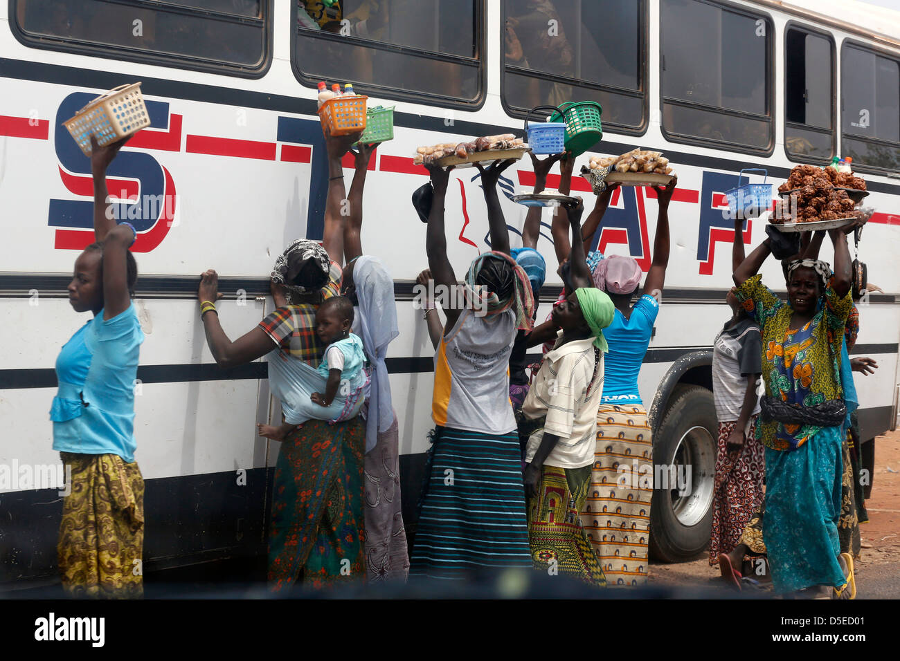 Street sellers try to selling refreshments and fruits to bus passengers, Burkina Faso, Africa - Stock Image