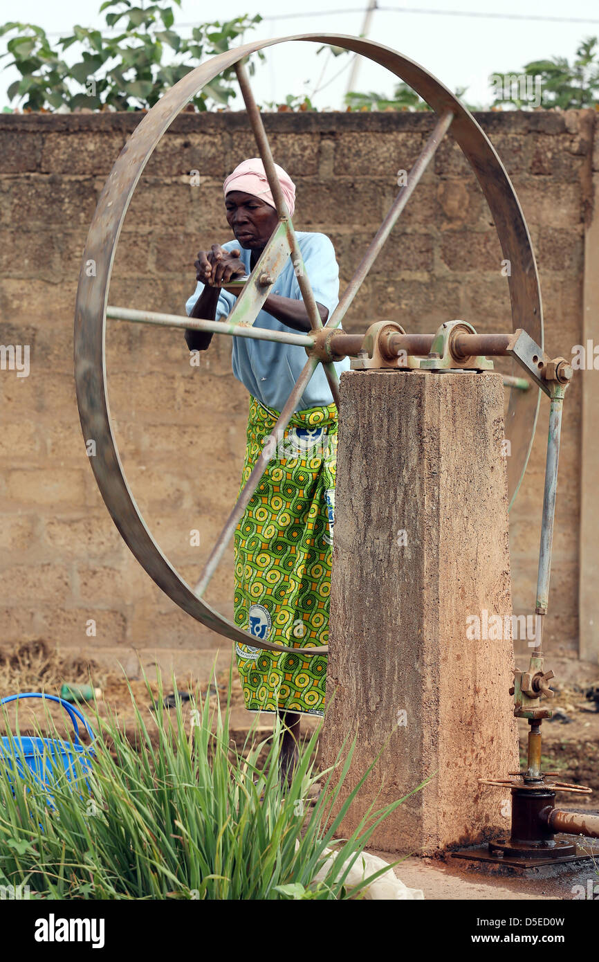 old woman pumps water from a well, Burkina Faso, Africa - Stock Image