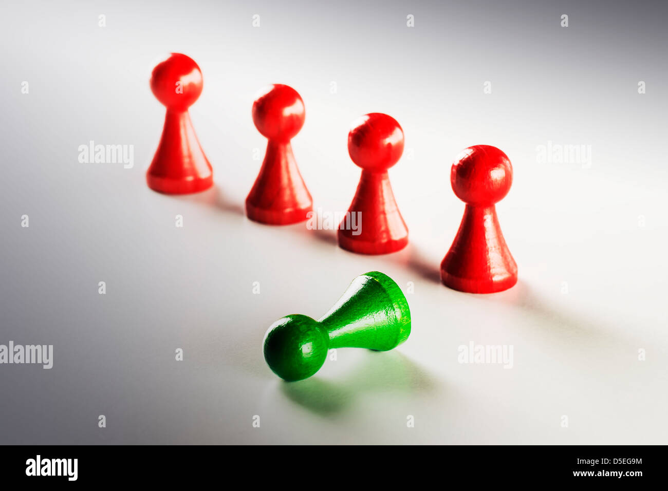 four red and one green lying standing human figure Ludo - Stock Image