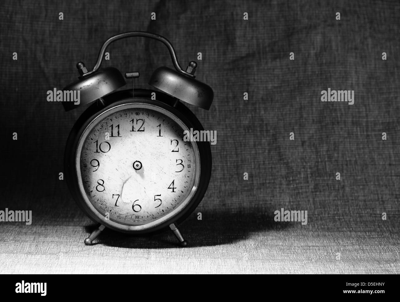 close-up of old broken alarm clock without clock hands on textile background with copy space for your text - Stock Image